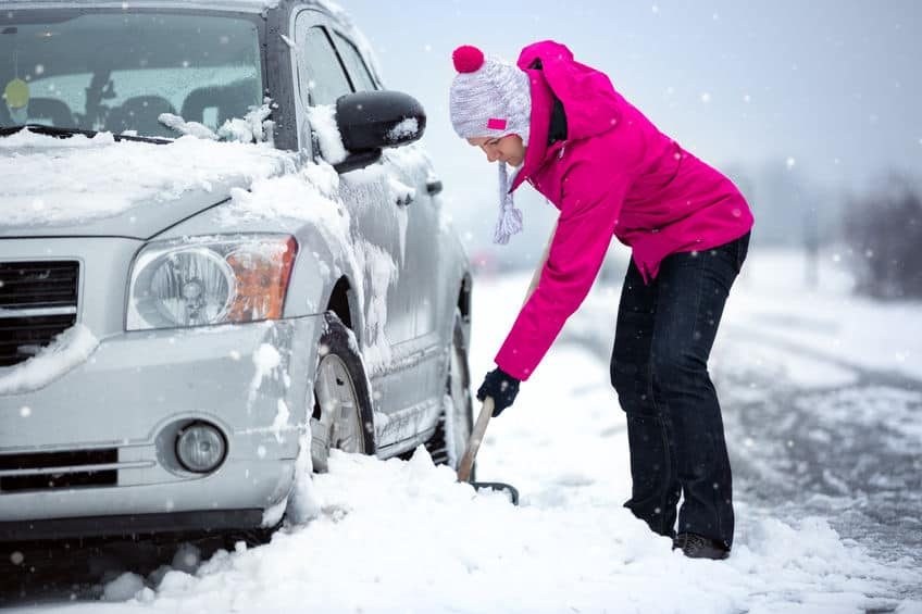 Woman shovels her car out of the snow. Winter driving preparedness.